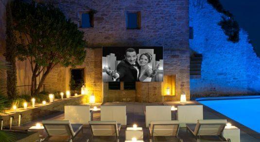Open-Air-Kino mit großer Leinwand neben dem Schwimmbad.