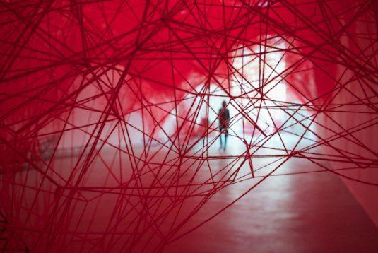 Ein Spinnennetz aus tausenden roten Fäden von der Japanerin Chiharu Shiota in der Joseph-Kirche
